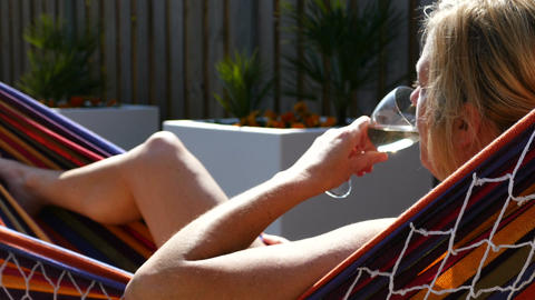 Blonde woman relaxes in a hammock enjoying a glass of wine Footage
