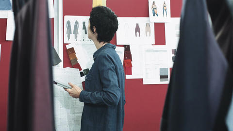 Fashion designer looking at designs in studio Live Action