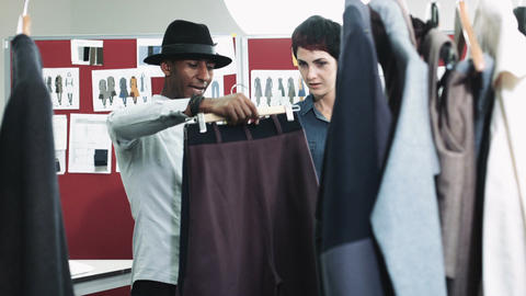 Fashion designer looking at clothes in studio Footage