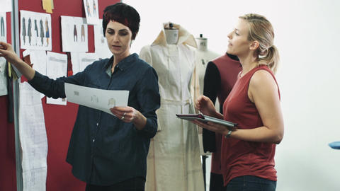 Fashion designers looking at digital tablet and clothes in studio Footage