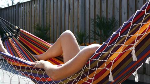 Blonde woman relaxes in a hammock in garden Footage