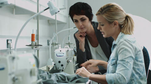 Fashion designers at sewing machine working together Footage
