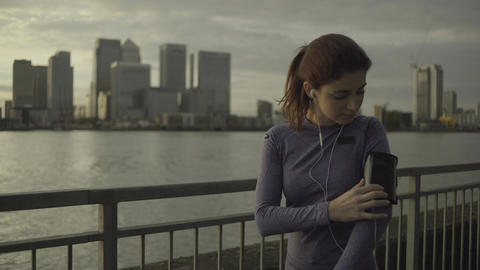 Female runner with headphones jogging by Thames River, London Footage