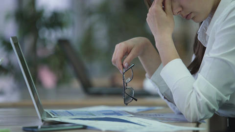 Exhausted woman manager taking off glasses and rubbing eyes, overworked employee Footage