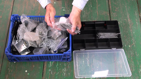 worker sorting nails in new plastic box Filmmaterial