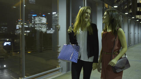 Female friends walking with shopping bags in city at night Footage