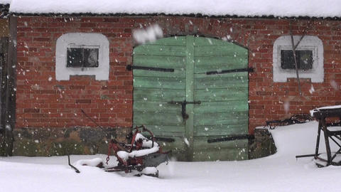 farm green door on red wall and winter snowfall Footage