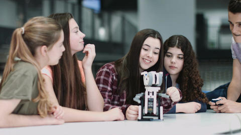 Five Children working with small robot at school GIF