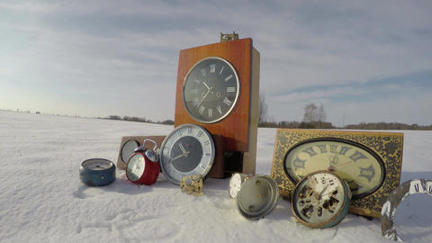 Old vintage clock collection on snow in field and clouds motion, time lapse 4K Footage