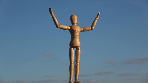 Wooden drawing manikin rotating on blue sky background, 4K Footage