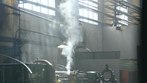 Camera Moves up Milling Machine Operating at Steam Puffs Footage