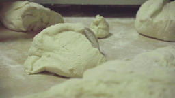 Dough at table on bakery HD video. Baker hands take dough. Bread production Footage