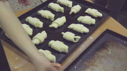 Raw croissant on tray before baking HD video. Baker at bakery prepares pastry Footage