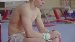 Young gymnast sitting in gymnasium HD video. Athlete emotional look 画像