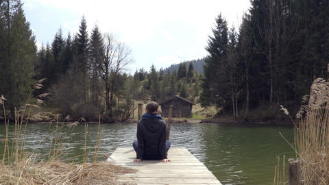 Person sitting on the piers on the lake in spring time Footage
