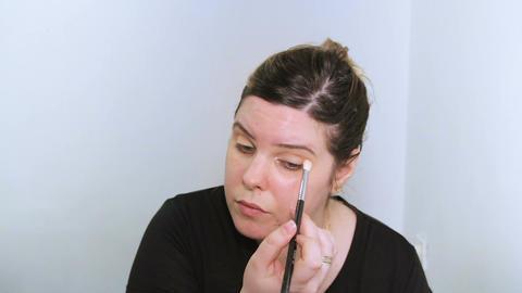 Beautiful young woman applying makeup Live Action