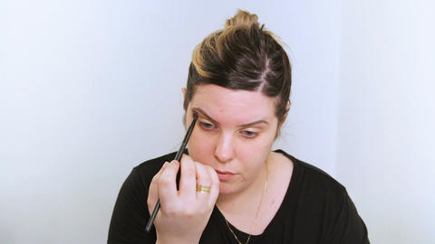 Beautiful young woman applying makeup Footage