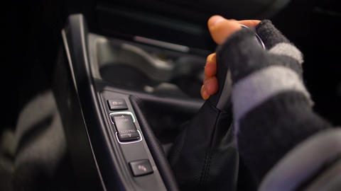 Man in gloves switching gearbox in expensive car, carjacking, offender Footage