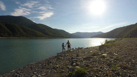 Couple strolling along bank of sunlit river holding hands, mountains on horizon Footage