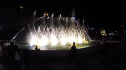 Silhouettes of people near illuminated fountain, water splashing in the air Footage