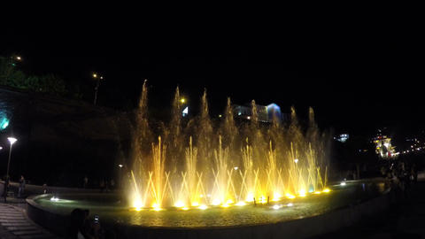 Illuminated fountain, water jets crisscrossing and going up, splashes in air Footage