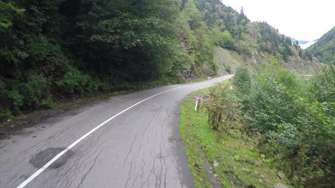 Narrow winding road in mountains surrounded by trees, dangerous driving Footage