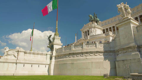 Flags waving in front of marble palace and Altar of the Fatherland in Rome Footage