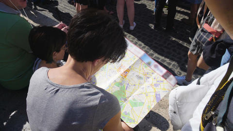 Female tourist looking at map and talking to husband, family vacation planning Footage