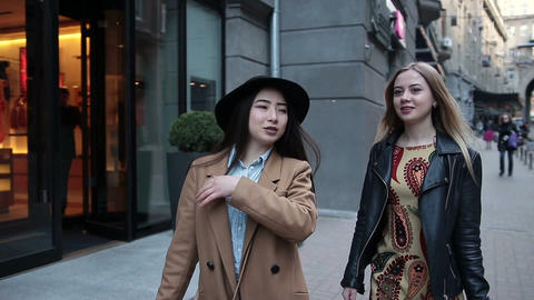 Two young women with shopping bags walking in city Footage
