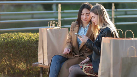 Two female friends shopping online with smartphone Footage