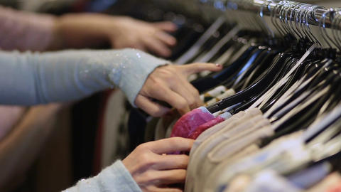 Female hands selecting colorful clothes on hangers Footage