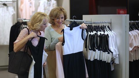 Two senoir women at boutique choosing dress Footage