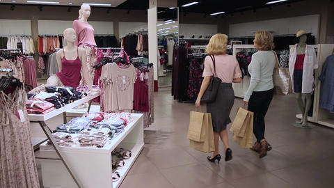 Shopper women selecting clothes in clothing shop Live Action