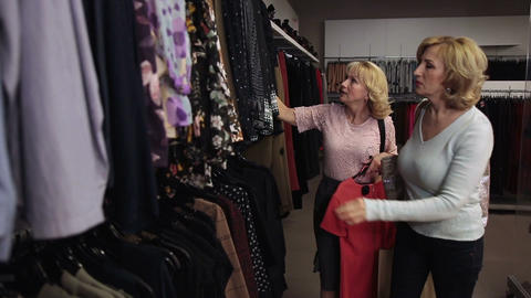 Happy blond women looking through clothes on rack Footage