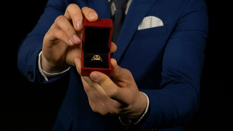 Hands of elegant man holding and presenting jewelry box with ring inside Footage
