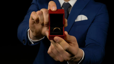Hands of young man opening ring box with wedding ring inside for wedding anniver Footage