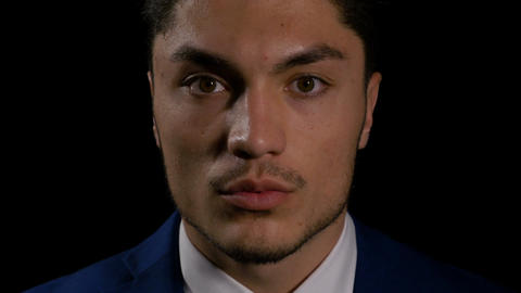 Close up of young successful man looking down and then straight into the camera Live Action