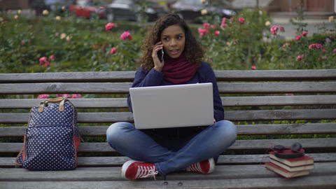 Excited female communicating with boyfriend on the phone, studying on bench Footage