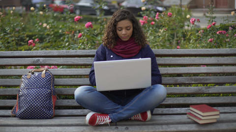 Charming biracial woman sitting on bench outdoors, working on laptop, freelancer Footage