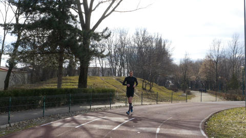 Man jogging in the park on the course track with closeup view of his legs Footage