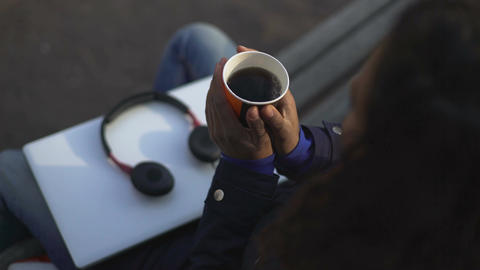 Woman warming hands, holding cup with fragrant hot drink while sitting outdoors Footage