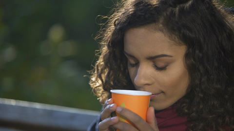 Young curly-haired woman enjoying taste of favorite morning coffee outdoors Footage