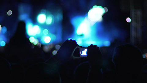 Hands of man holding smartphone in air to film video of concert atmosphere Footage
