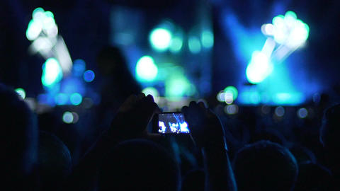 Man using gadget camera to film video from concert, silhouettes of audience Live Action
