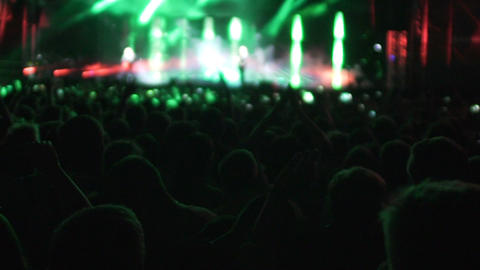 Silhouettes of people watching performance by singer, bright lights on stage Footage