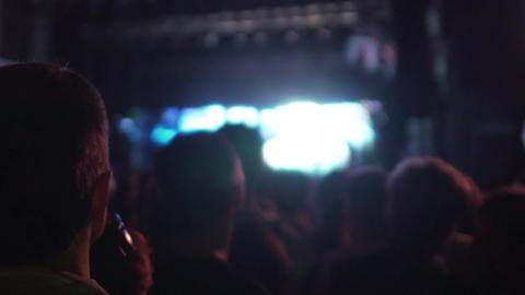 Back view of many people watching performance on illuminated stage, concert Footage