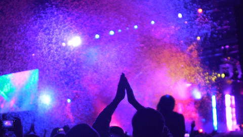 Human silhouettes applauding, watching amazing colorful light and confetti show Footage