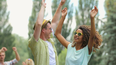 Young man and woman dancing at outdoor music fest with their hand up in the air Footage