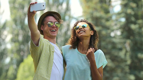 Young couple taking picture of themselves while hugging and dancing together Footage