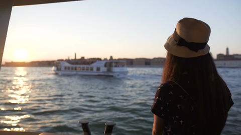 Beautiful female tourist travelling by water taxi, looking at cityscape at dusk Footage
